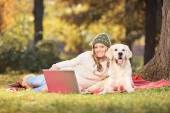 Woman with dog and laptop in a park — Stock fotografie