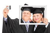 Mature couple taking selfie behind picture frame — Stock Photo