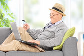 Senior with laptop and credit card — Stock Photo