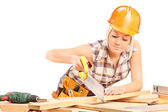 Female carpenter cutting plank with handsaw — Fotografia Stock