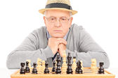 Senior contemplating next move in chess — Stockfoto
