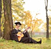 Graduate student playing acoustic guitar — Stock Photo