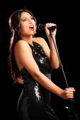 Female singer singing on microphone — Stockfoto