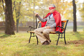 Senior in superhero outfit in park — Stock Photo