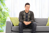 Young man seated on sofa — Stock Photo