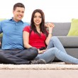 Young couple seated on carpet — Stock Photo #65155955