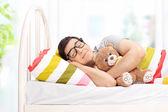 Bir oyuncak ayı ile uyuyan adam — Stok fotoğraf