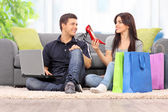 Woman showing shoes to boyfriend — Stock Photo