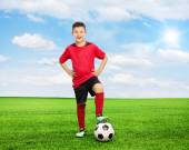 Youngster standing over a football — Stock Photo
