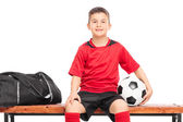 Junior soccer player sitting on a bench — Stock Photo