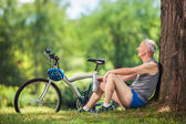 Active senior listening to music seated by a tree in park — Stock Photo