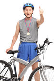 Senior cyclist with a medal giving a thumb up — Stock Photo