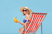 Woman sitting in a sun lounger — Stock Photo