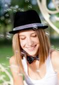 微笑的女人和肥皂泡沫的年轻人 — 图库照片
