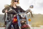 Biker girl in  leather jacket on a motorcycle looking at the sunset. — Foto de Stock