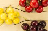 Colorful cherries in a wooden spatula on a natural fabric — Stock Photo