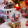 New year decorations of candles, cones and snow globe with santa claus and girl — Stock Photo #60835181