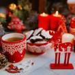 New year decorations with cup of tea, cakes, candles, cones and wooden deer — Stock Photo #60992873