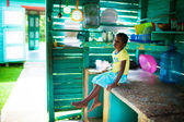 Young boy sits in the kitchen and sings, Dominican Republic — Stock Photo
