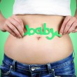 Close-up portrait of a womans stomach in early pregnancy and woman holding a green coloured word baby above her navel. — Stock Photo #53284057