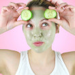 Beauty portrait of a funny woman wearing a pink headband, white top and a green facial mask is holding two slices of cucumber above her eyes. — Stock Photo #53722799