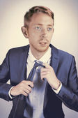 Attractive sophisticated young businessman with light hair wearing a navy blue suit and a tie is looking away and fixing his tie. — Stock Photo