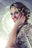 Beautiful smiling blonde woman with curly shoulder length hair wearing evening make-up and a golden sparkly sequin bolero. — Stock Photo