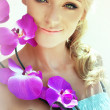 Sunny portrait of a smiling blonde woman with curly hair wearing a strapless summer dress and golden smoky eye make-up is holding a bright purple orchid close to her face. — Photo #57462707