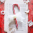 Candy cane with a lacy bow on a torn book page on red background surrounded by paper snowflakes. — Stock Photo #59638381