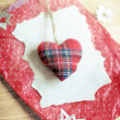 Stuffed soft tartan fabric Christmas heart on a torn piece of paper and red dotted crinkled wrapping paper surrounded by paper snowflakes on a wooden surface. — Stockfoto #59638405