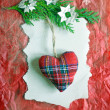 Soft stuffed Christmas tartan heart hanging on a green branch covered with paper snowflakes on a red crinkled paper surface. — Stock Photo #59638453