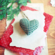 Stuffed soft green checked Christmas heart on a torn piece of paper and red dotted wrapping paper surrounded by paper snowflakes and a green tree branch on a wooden surface. — Stock Photo #59638481