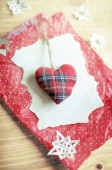 Stuffed soft tartan fabric Christmas heart on a torn piece of paper and red dotted crinkled wrapping paper surrounded by paper snowflakes on a wooden surface. — Stock Photo