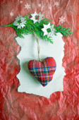 Soft stuffed Christmas tartan heart hanging on a green branch covered with paper snowflakes on a red crinkled paper surface. — Stock Photo