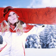 Attractive female snowboarder wearing red and white sports outfit is holding her snowboard on her shoulders in a snowy winter forest. — Stock Photo #59685163