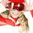 Cheerful blonde female snowboarder wearing red and white sports outfit is playing with her goggles. — Stock Photo #59685175