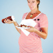 Funny pregnant woman is holding a ketchup bottle and looking at a plate with food in front of her with big surprised eyes. — Stock Photo #59685909