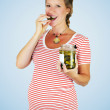 Young pregnant woman eating pickled cucumber straight from the jar in her hand. — Stock Photo #59685931