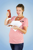 Funny pregnant woman is squeezing lots of ketchup on her food with a mischievous smile on her face. — Stock Photo