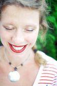 Close-up portrait of a happy young woman wearing red lipstick and natural eye make-up is laughing with her eyes closed. — ストック写真