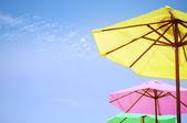 Bright multi coloured umbrellas on the beach. — Stock Photo