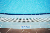 Empty swimming pool with rippled clean blue water in holiday resort. — Stock Photo