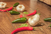 Garlic between jalapenos and chili peppers — Stok fotoğraf
