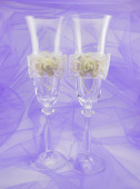 Two beautiful wedding glasses with flowers on a purple backgroun — Stockfoto