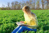Girl reading a book in a field — Stock Photo