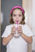 Little girl drinking a glass of milk — Stock Photo