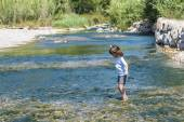 Little girl crossing a river — Stock Photo