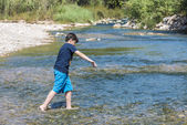 Boy crossing a river — Stock Photo