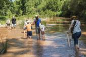 Family crossing a river — Stock Photo