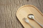 Spoon and fork on a background of brown wood. — Stock Photo
